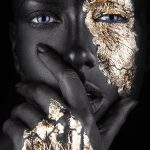 fashion portrait of a dark-skinned girl with gold make